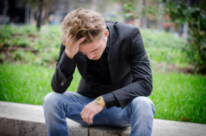 Depressed Young White Man Sitting at Street Side